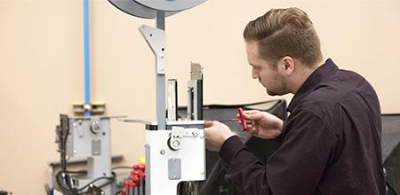 Kwik Lok employee working on machine parts